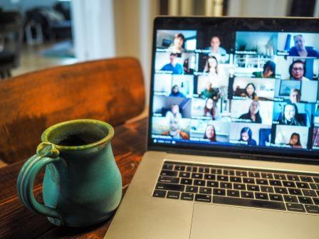 Laptop open with coffee mug next to it. People video conferencing on screen,