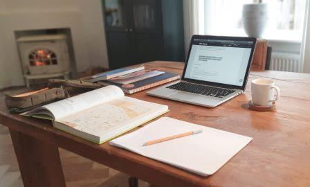 Desk ready for WFH with open laptop, coffee mug, pen, paper and books.
