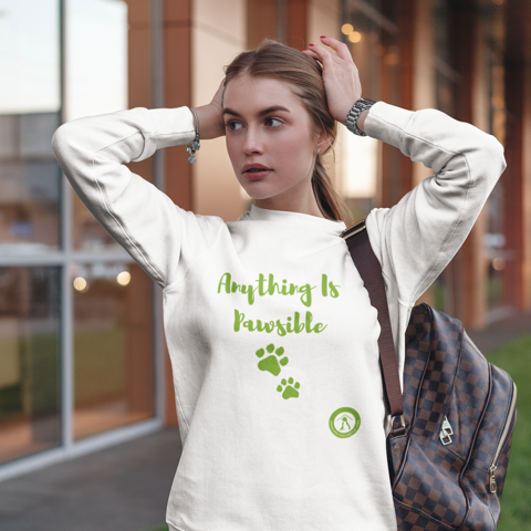 Lady wearing white sweatshirt with Anything is Pawsible written in green with green pawprints below it