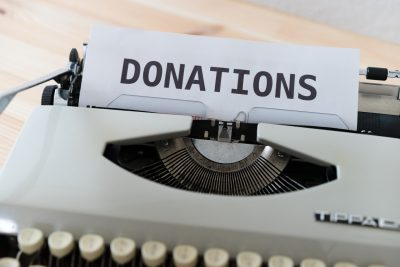 Typewriter with paper and donations printed on it