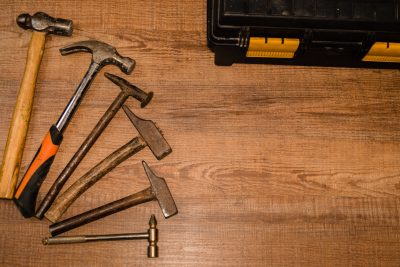 Picture of a wooden work bench with selection of hammers spread out on it